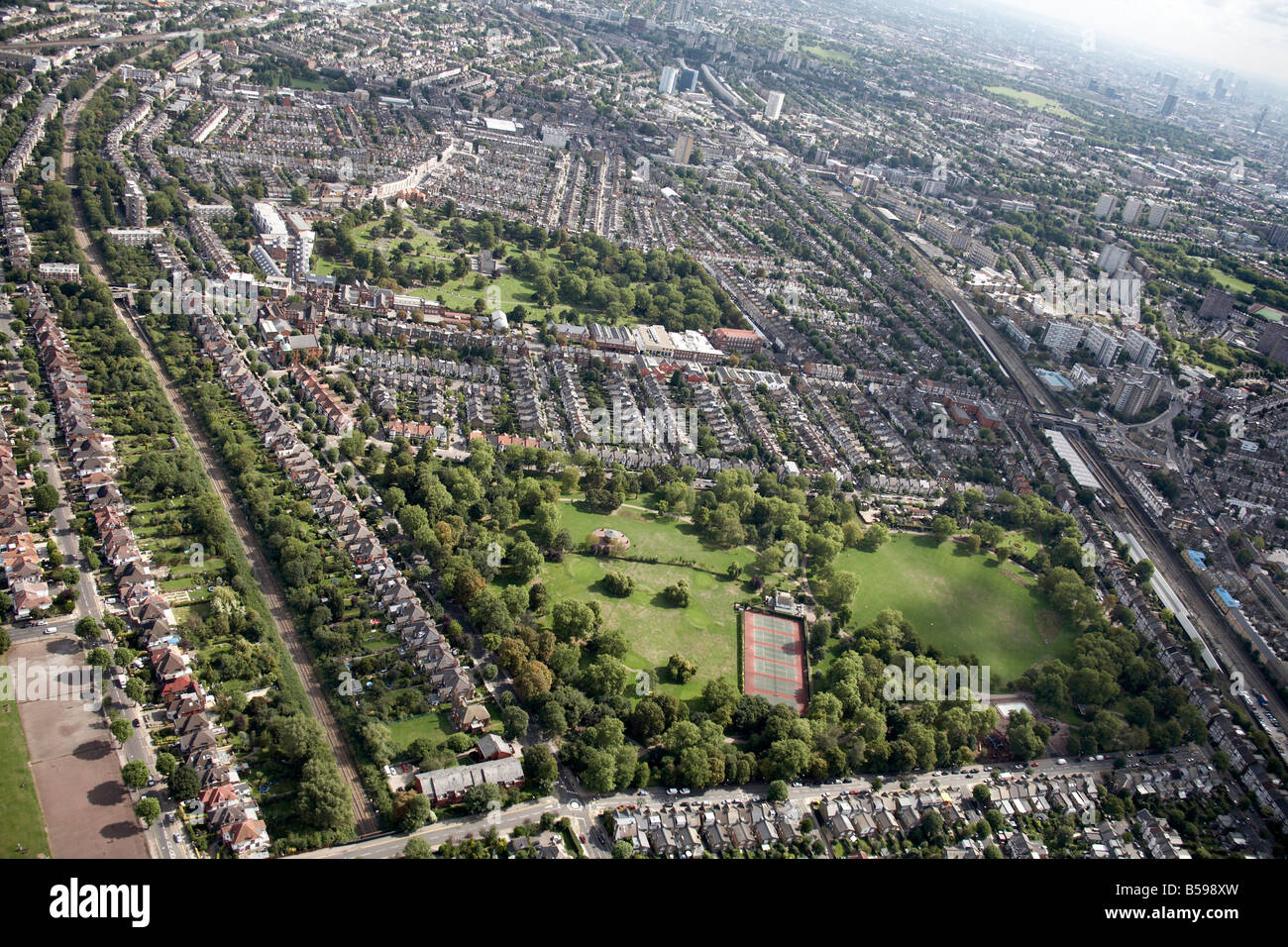 Aerial view north east of Queens Park tennis courts Willesden Lane Cemetery railway line suburban houses tower blocks - Stock Image