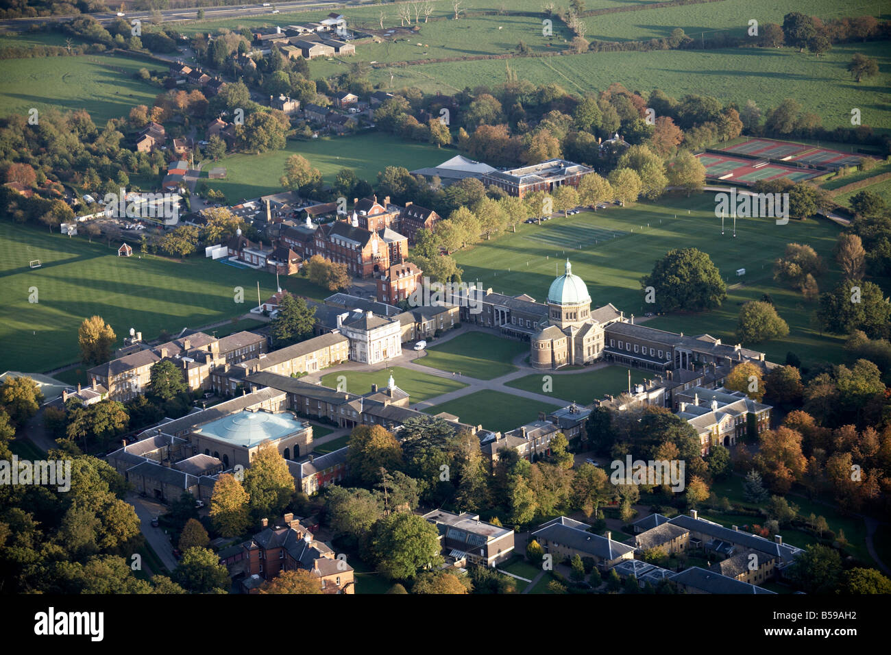 Aerial view south east of Haileybury College playing fields trees tennis courts suburban houses Hertfordshire SG13 - Stock Image