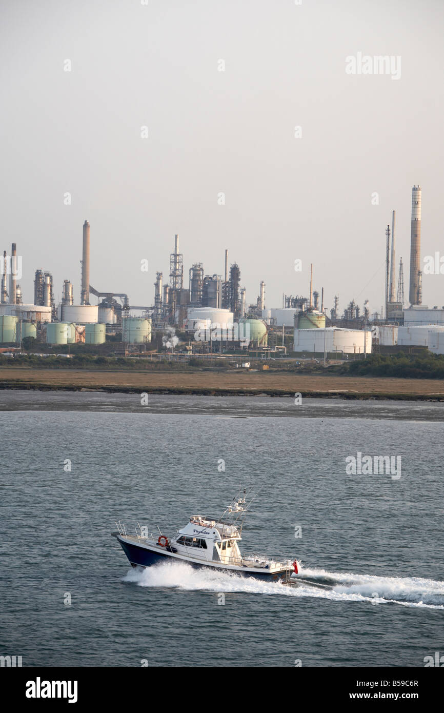 Fawley oil refinery and natural gas terminal and storage depot tanks with motor boat near Hythe Southampton Water Stock Photo