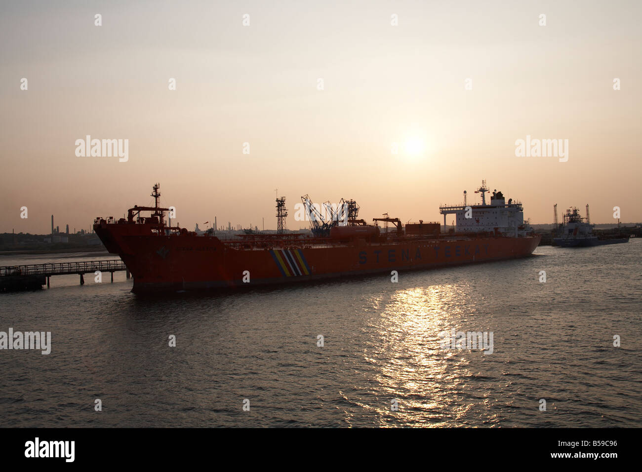 Merchant shipping vessels ships docked at Fawley oil refinery terminal port on Southampton Water in evening sunset - Stock Image