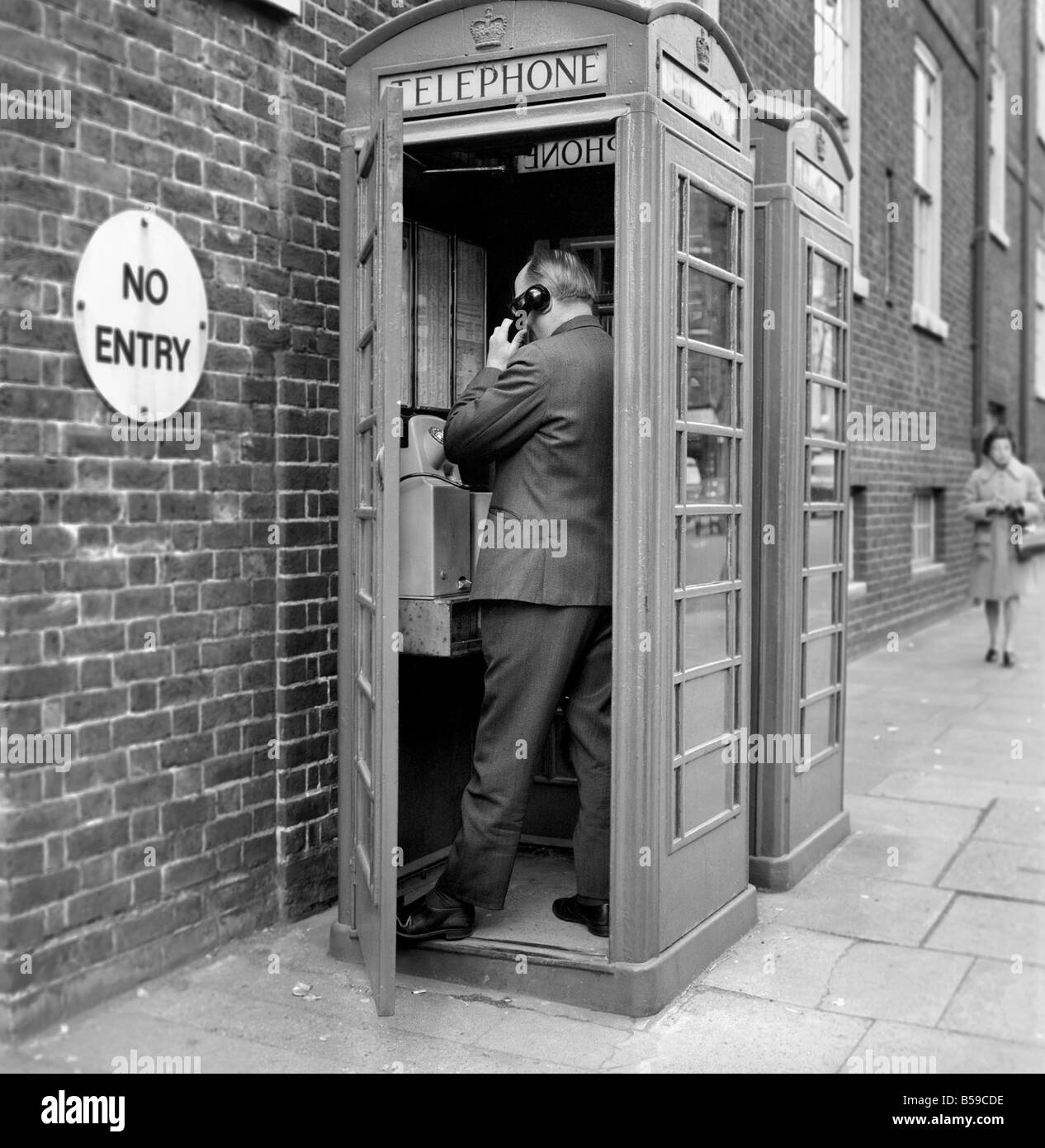 Man using a telephone box. The red telephone box was designed by Sir Giles Gilbert Scott, and up until the early - Stock Image