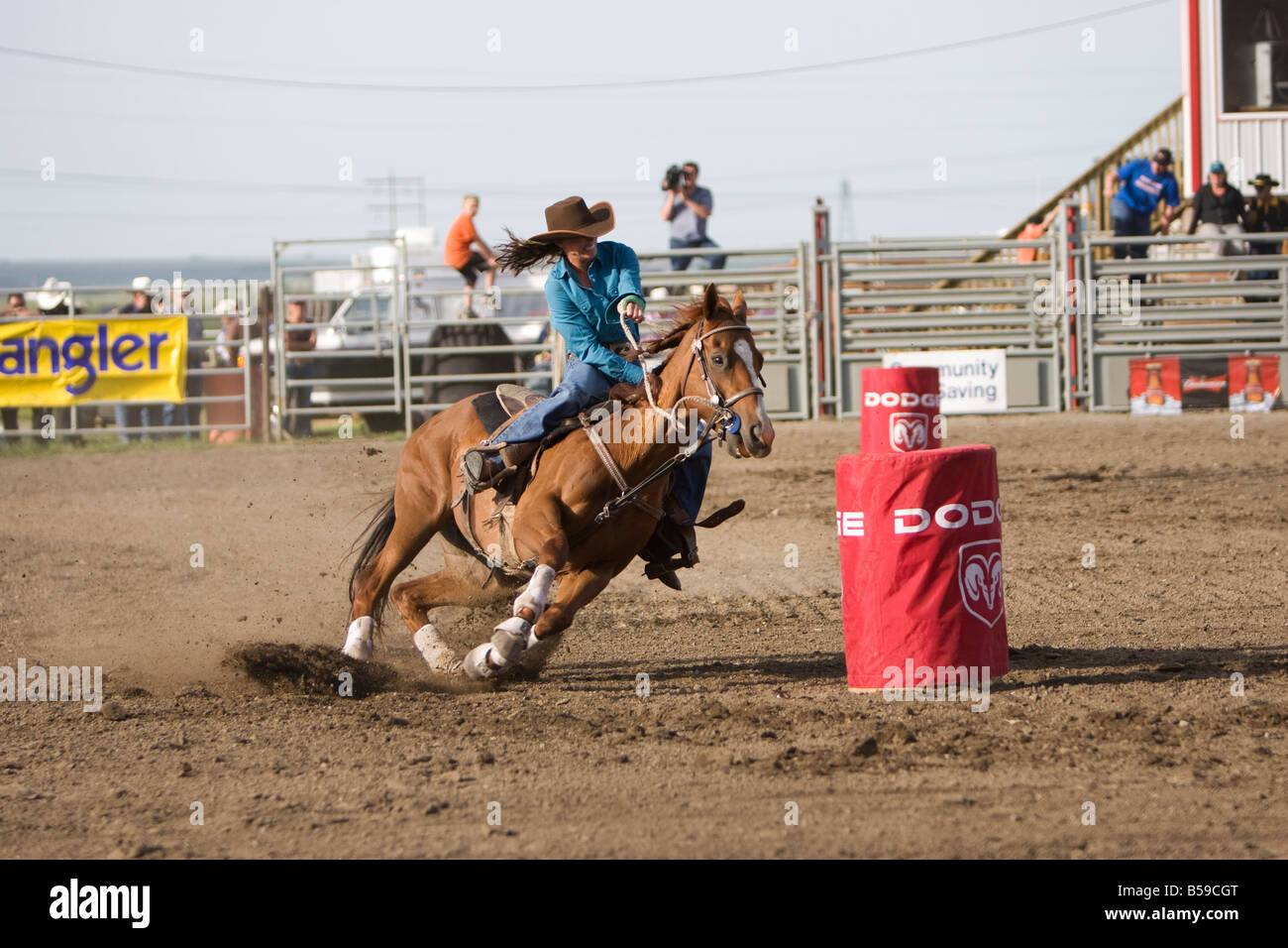 c960d49e8f1c5 A cowgirl barrel racing around a red barrel on a chestnut horse at a rodeo.
