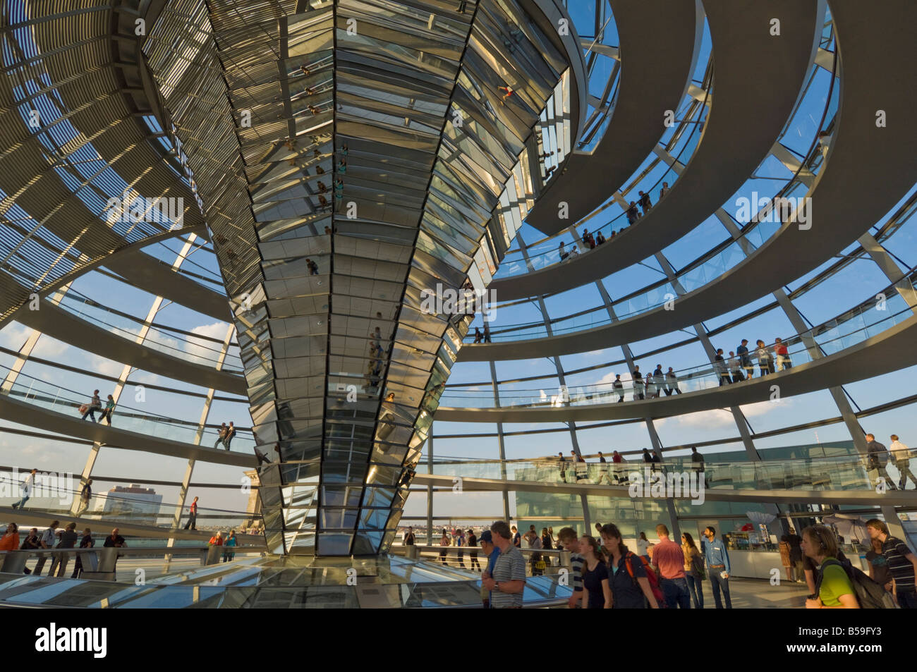 Visitors walk up a spiralling ramp around the cone shaped funnel in the dome cupola, Berlin, Germany Stock Photo