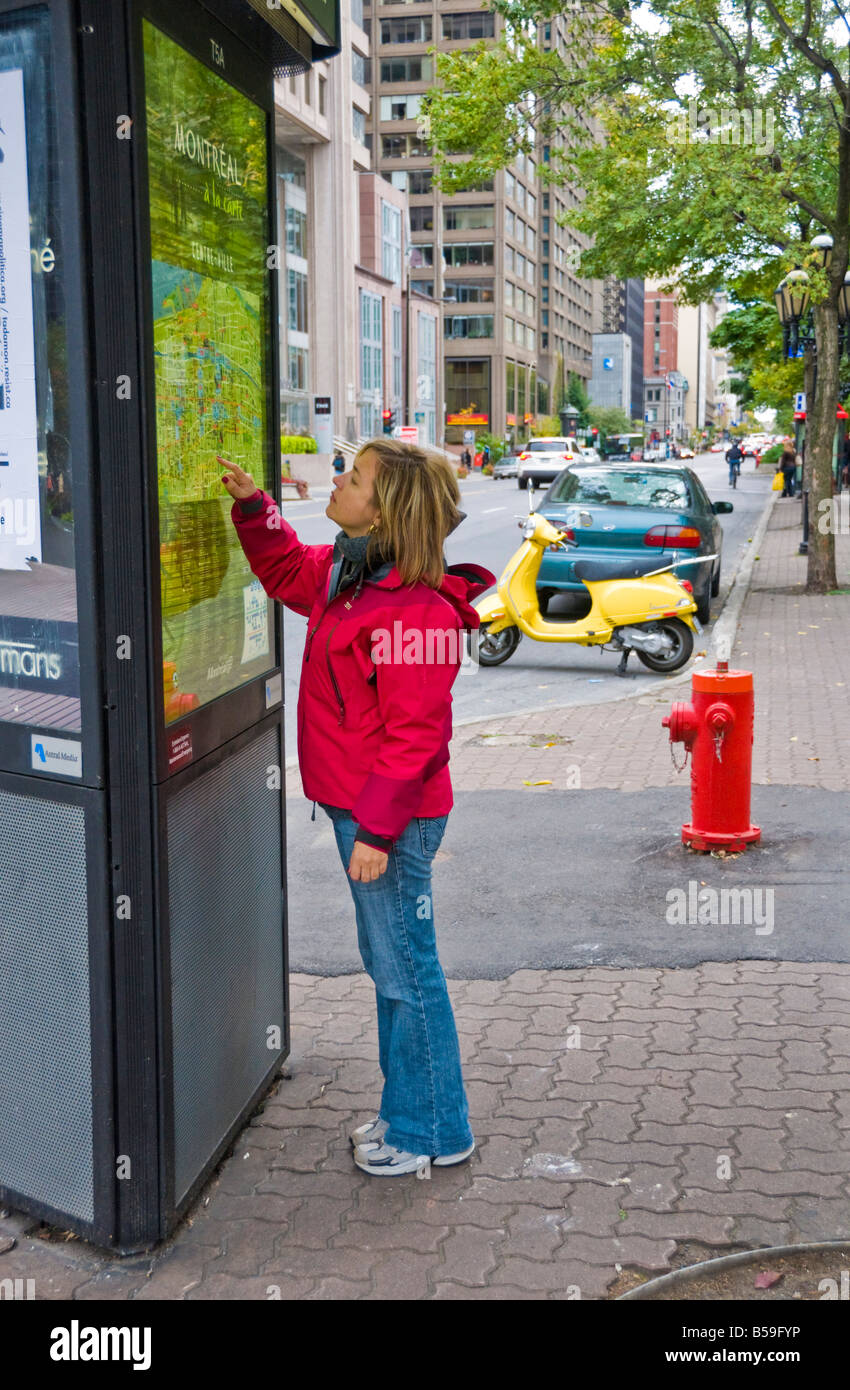 Tourist looking at Montreal map on Sherbrooke street montreal - Stock Image