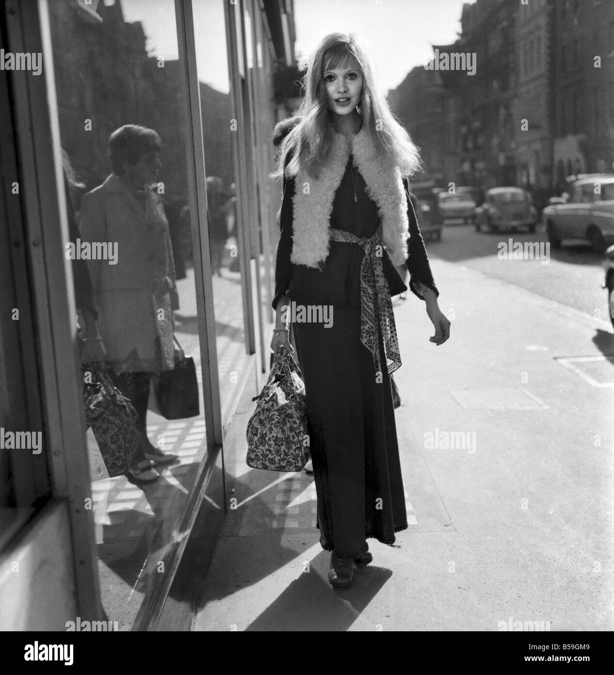 The first cool day and the maxi look seem to be the swinging London look. Actress Maddy Smith seen in Bond Street - Stock Image