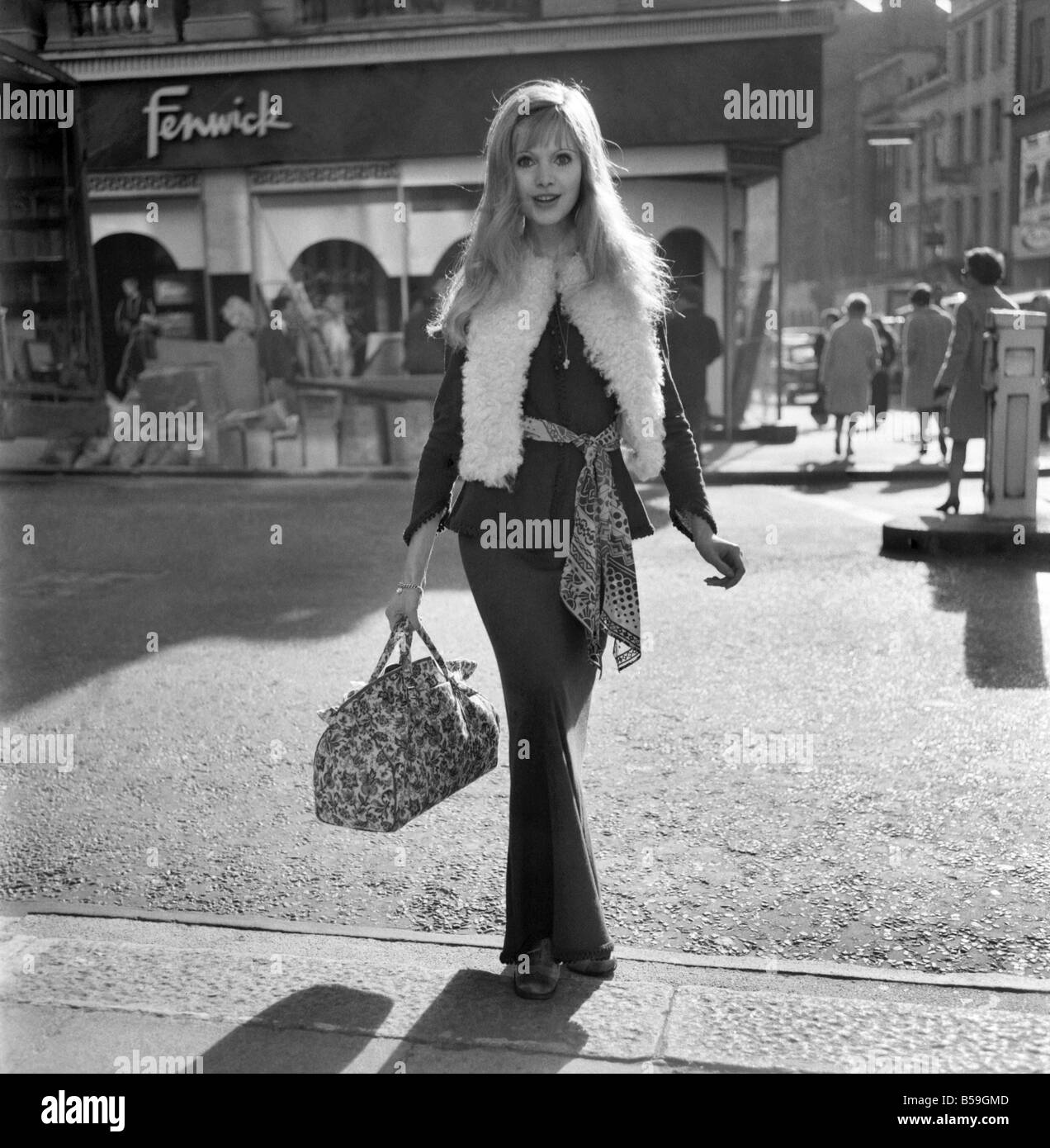 Fashion. Clothing. The first cool day and the maxi look seem to be the swinging London look. Actress Maddy Smith - Stock Image
