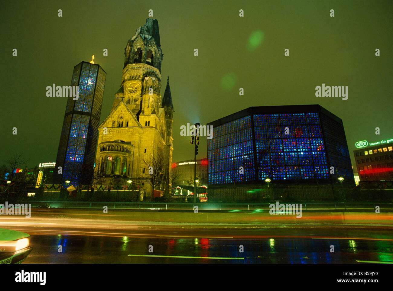Contrast of the Remembrance Church and the Kaiser Wilhelm Memorial Church, illuminated at night, Kurfurstendam, - Stock Image