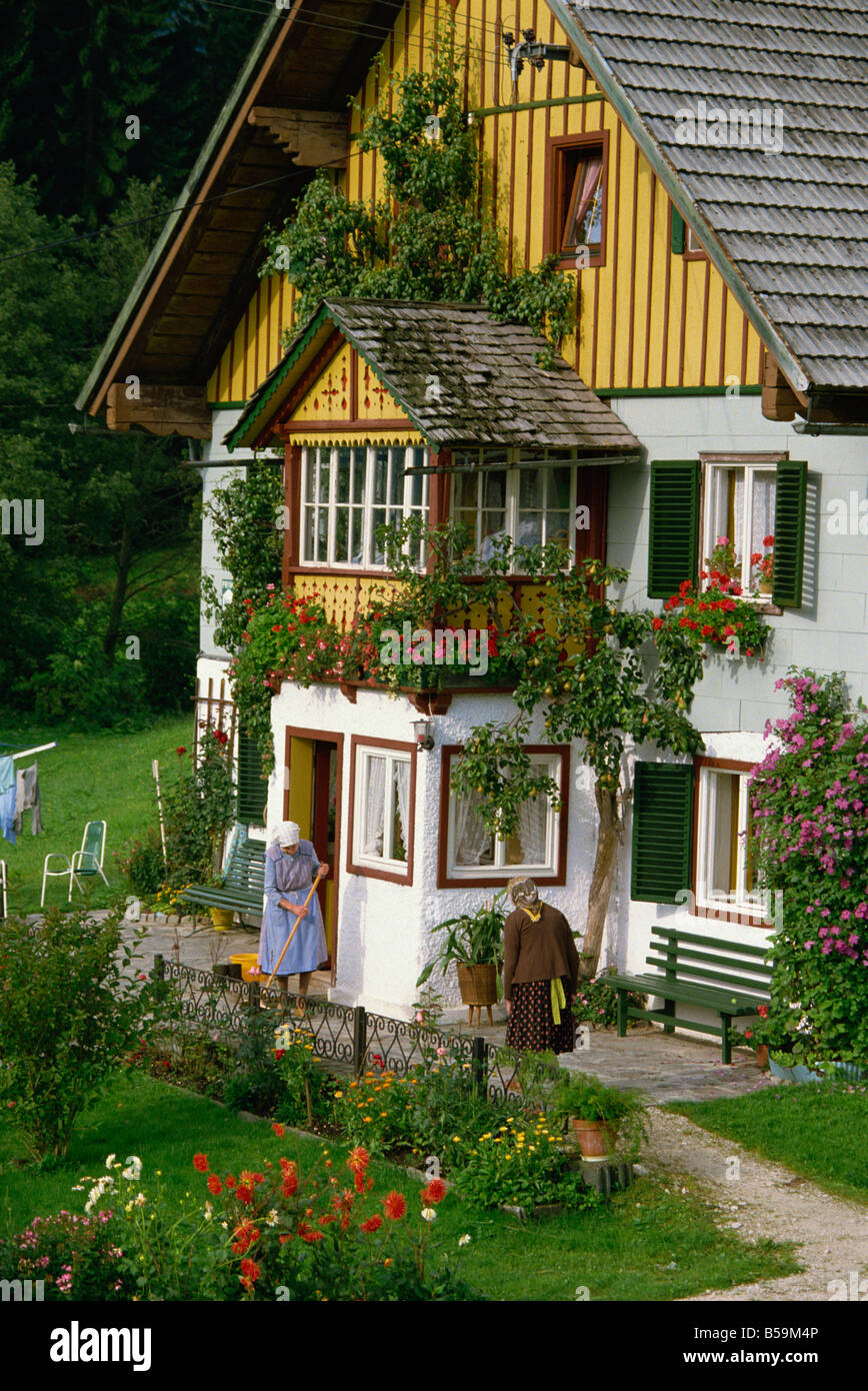 Two ladies outside a typical house with summer flowers in windowboxes and in the garden, in the Salzkammergut area - Stock Image