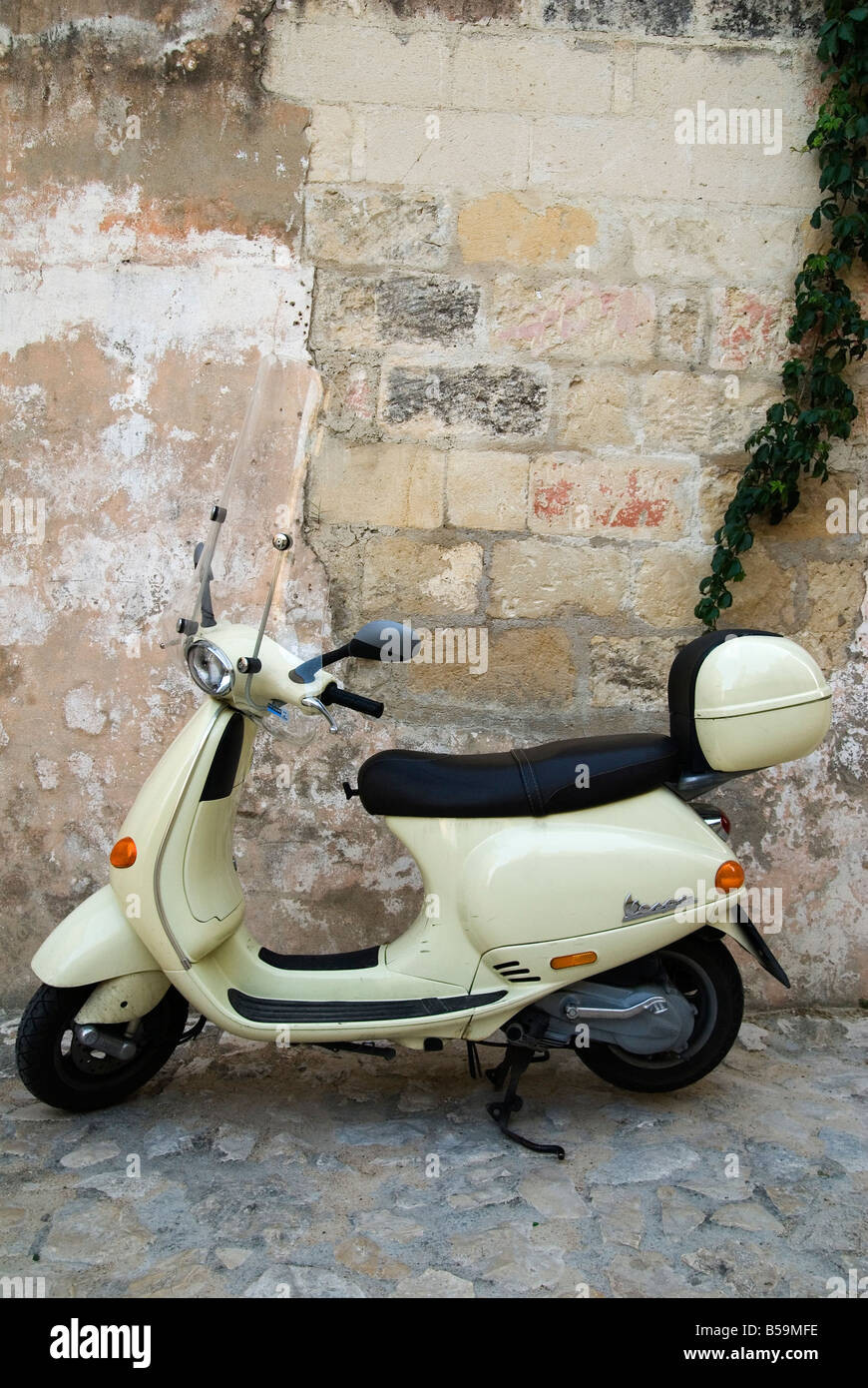 A retro styled Piaggio Vespa scooter parked in front of a weathered wall on a cobbled road in Matera, Basilicata, - Stock Image