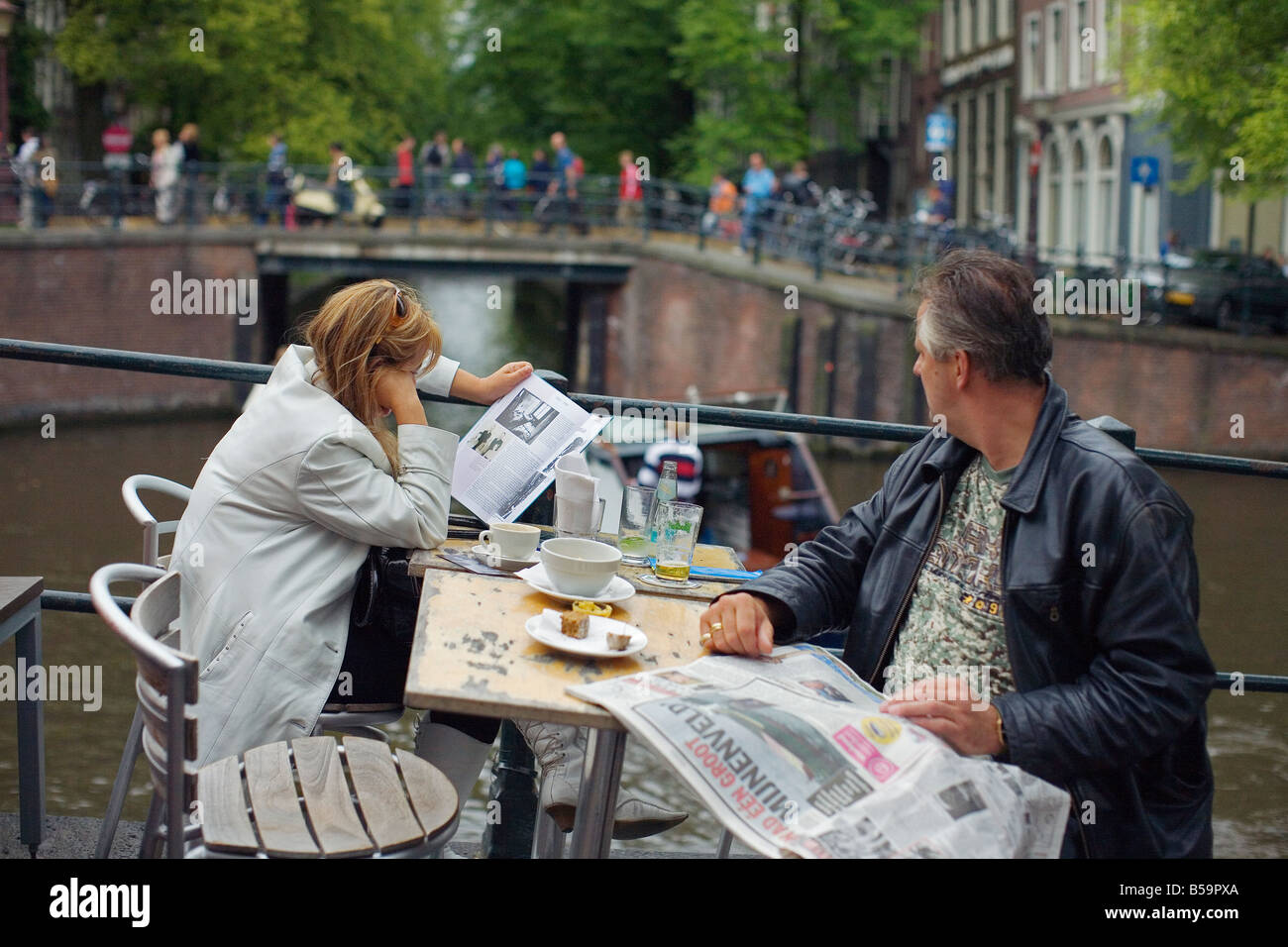 A Couple resting along an Amsterdam Canal,reading their newspapers and drinking Coffee. Stock Photo
