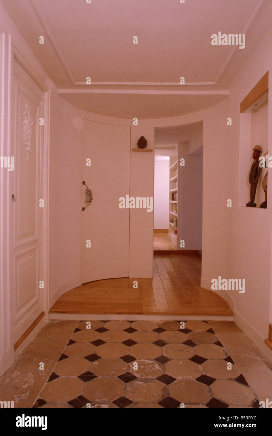 Terracotta floor tiles and wooden flooring in modern white hall with ...