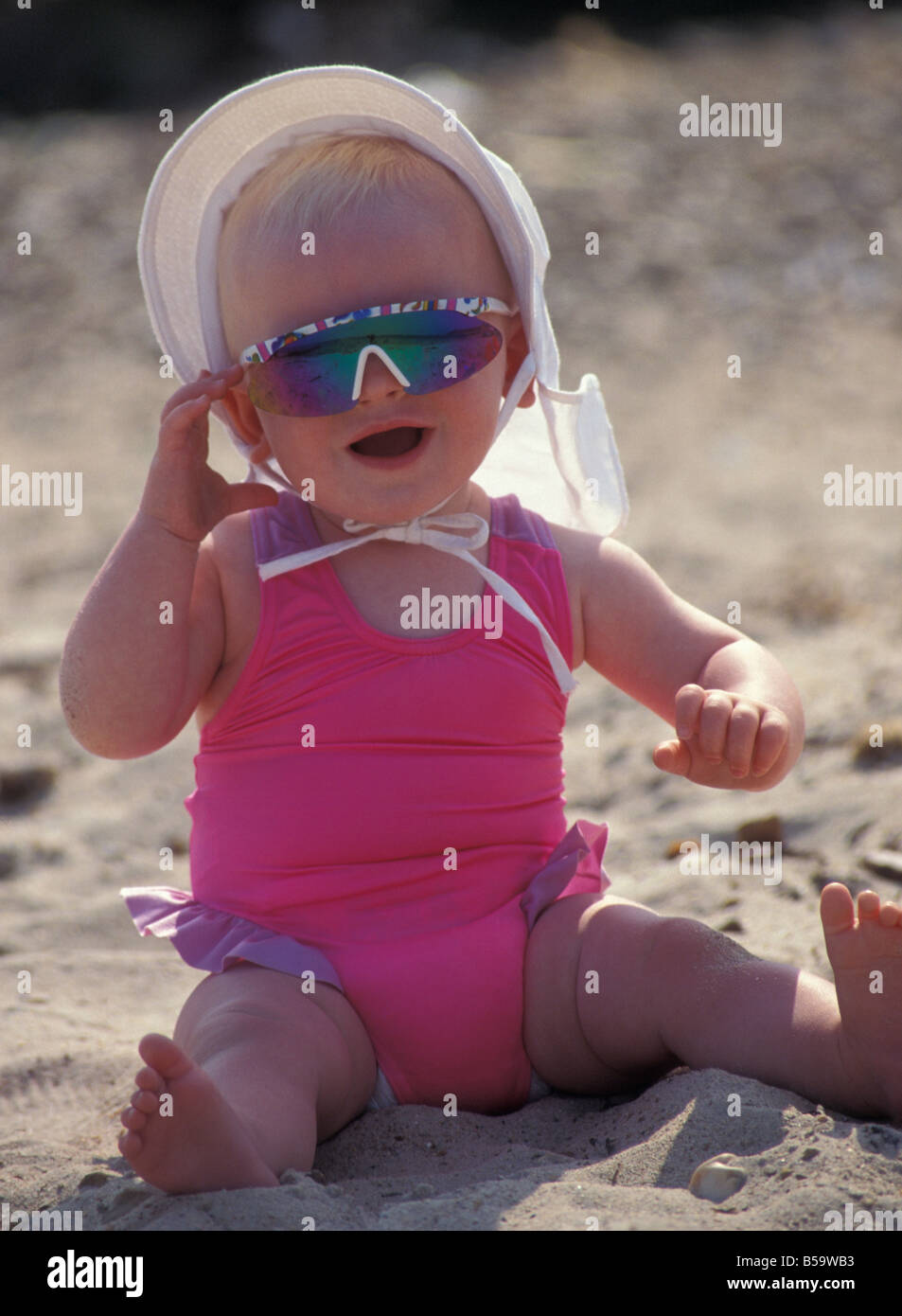 d7a98a5342f5 little baby girl sitting on beach in swimsuit wearing sunhat and sunglasses