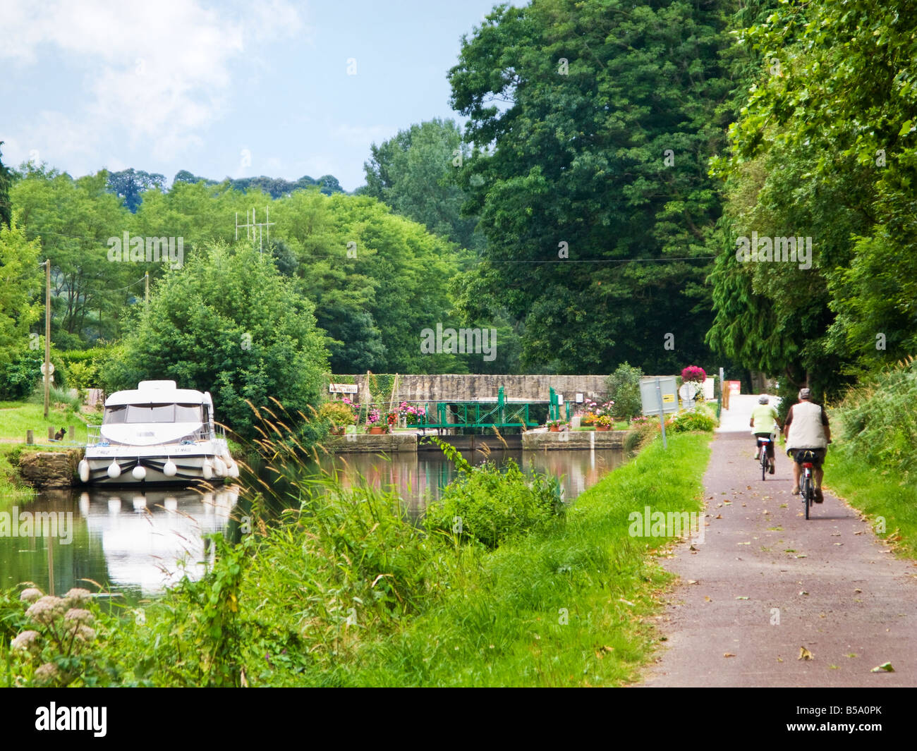 Cyclists on the towpath at a Lock on the Nantes Brest Canal at Cadoret, Morbihan, Brittany, France Europe - Stock Image