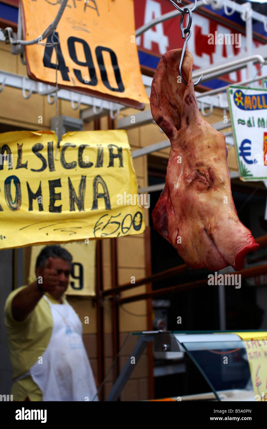 Butcher in Ballarò market in Palermo gives the thumbs up to his market produce behind a pigs head that has - Stock Image