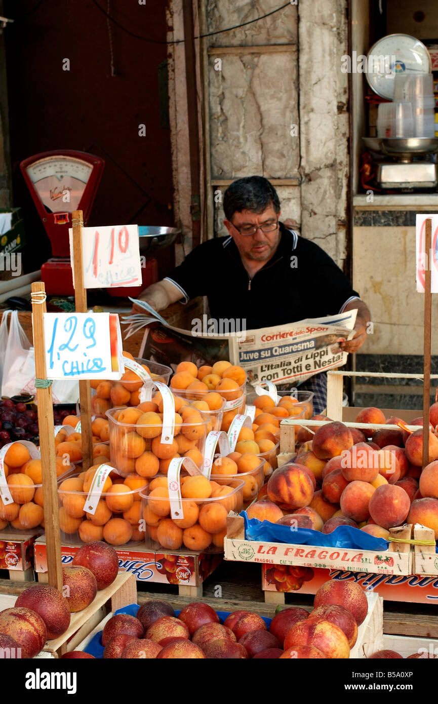 fruit seller in Ballarò market, Palermo takes moment to catch up the sports news, reading the Corriere dello - Stock Image