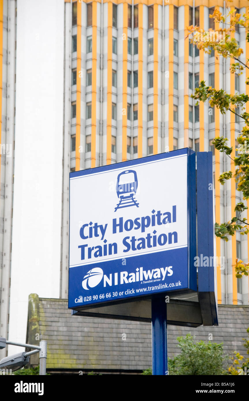 Belfast City Hospital train station sign in front of City Hospital tower block - Stock Image