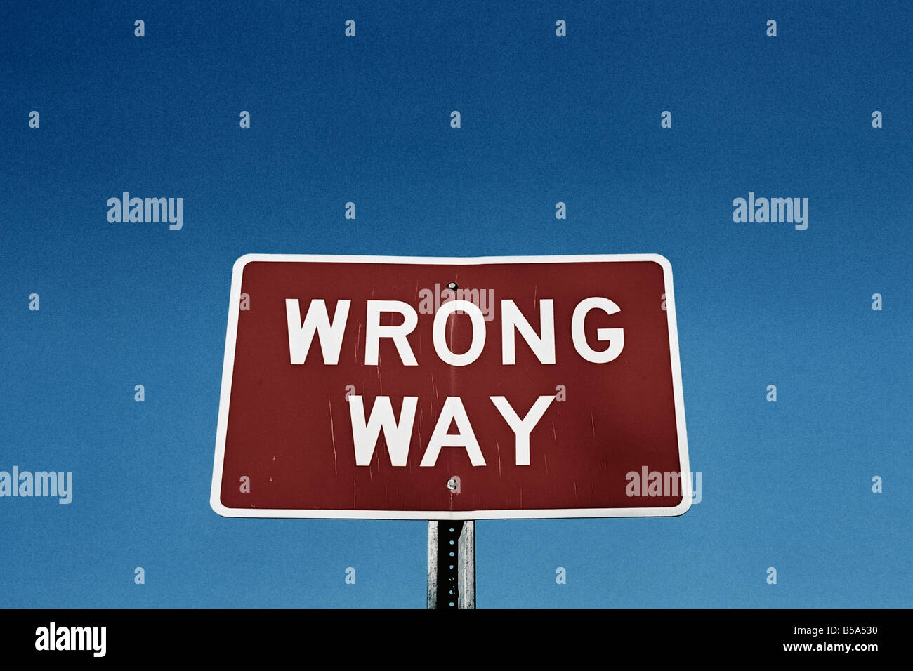 Wrong Way Road Sign Against Sky Low Angle View - Stock Image