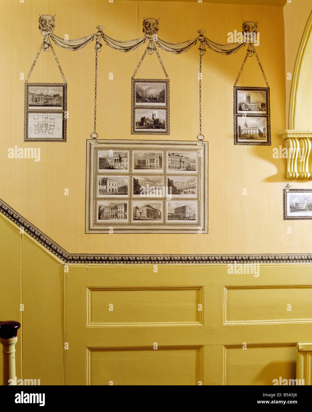 Decoupage black and white print room drawings above dado panelling in traditional yellow hall - Stock Image
