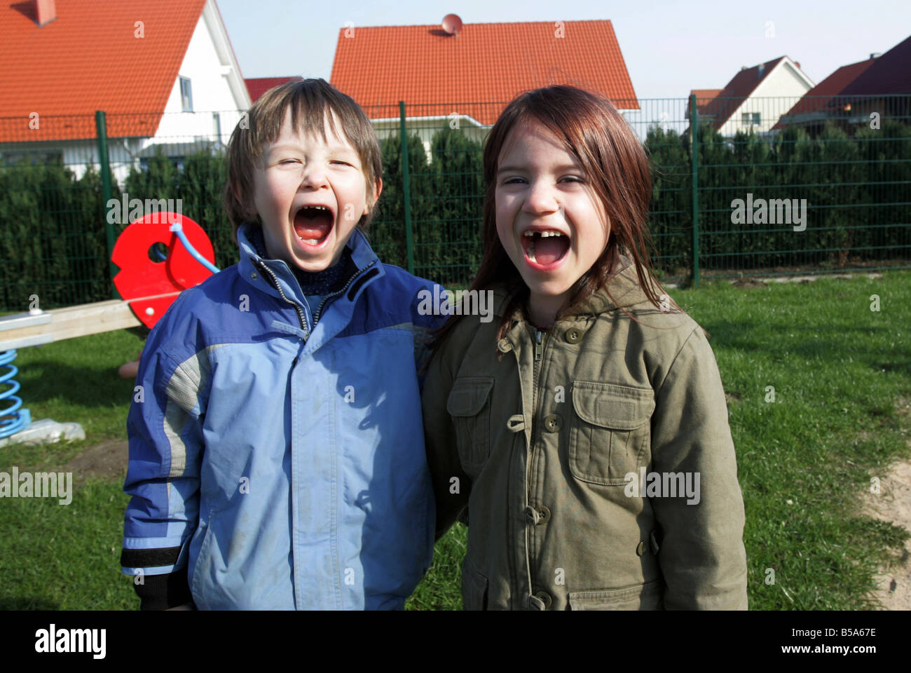 A boy and a girl screaming loudly - Stock Image