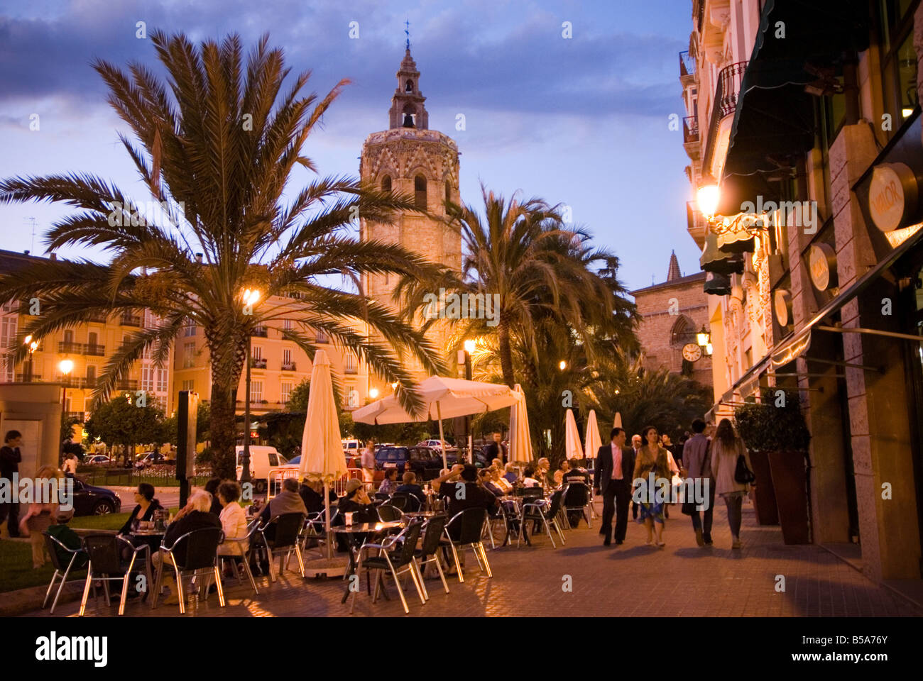 People sitting outside a busy bar on Plaza de la Reina with veiw to the Miguelete cathedral tower in El Carmen Valencia Stock Photo