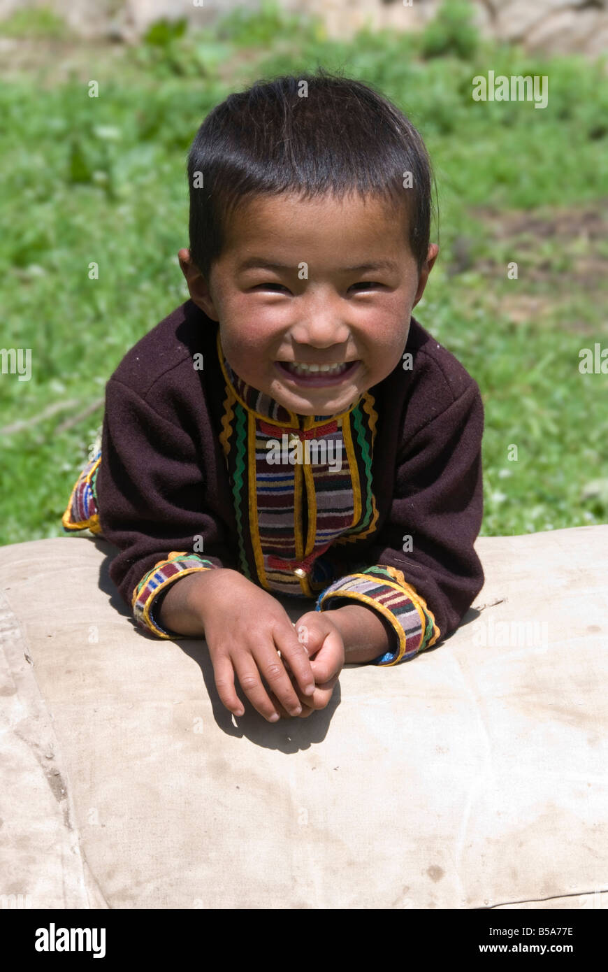 Smiling Tibetan child in a rural village on the nomadic grasslands in Sichuan, China. Stock Photo