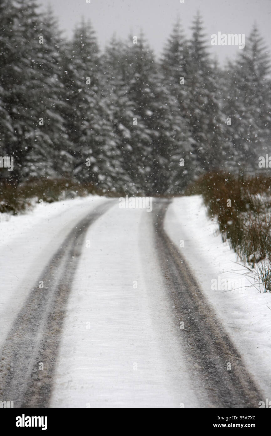 snow and ice on a remote rural mountain road running past a forest county antrim northern ireland uk - Stock Image