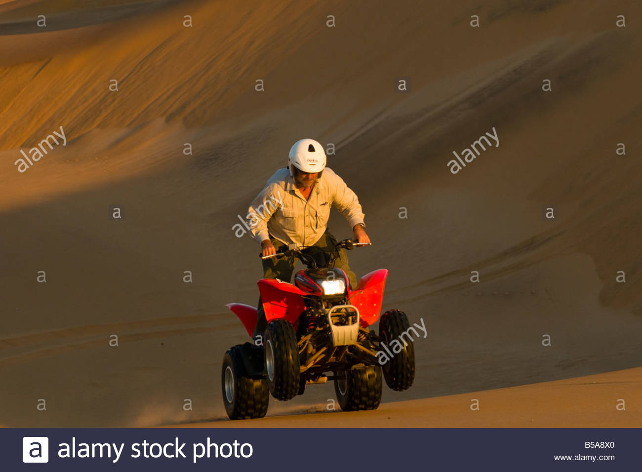 Riding Quad Bikes All Terrain Cycle in the Swakopmund Dunes Swakopmund Namib Desert Namibia - Stock Image