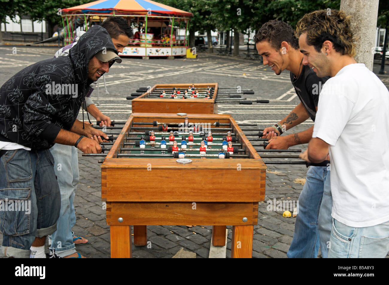 Four young men playing 'table football' in park outdoors - Stock Image