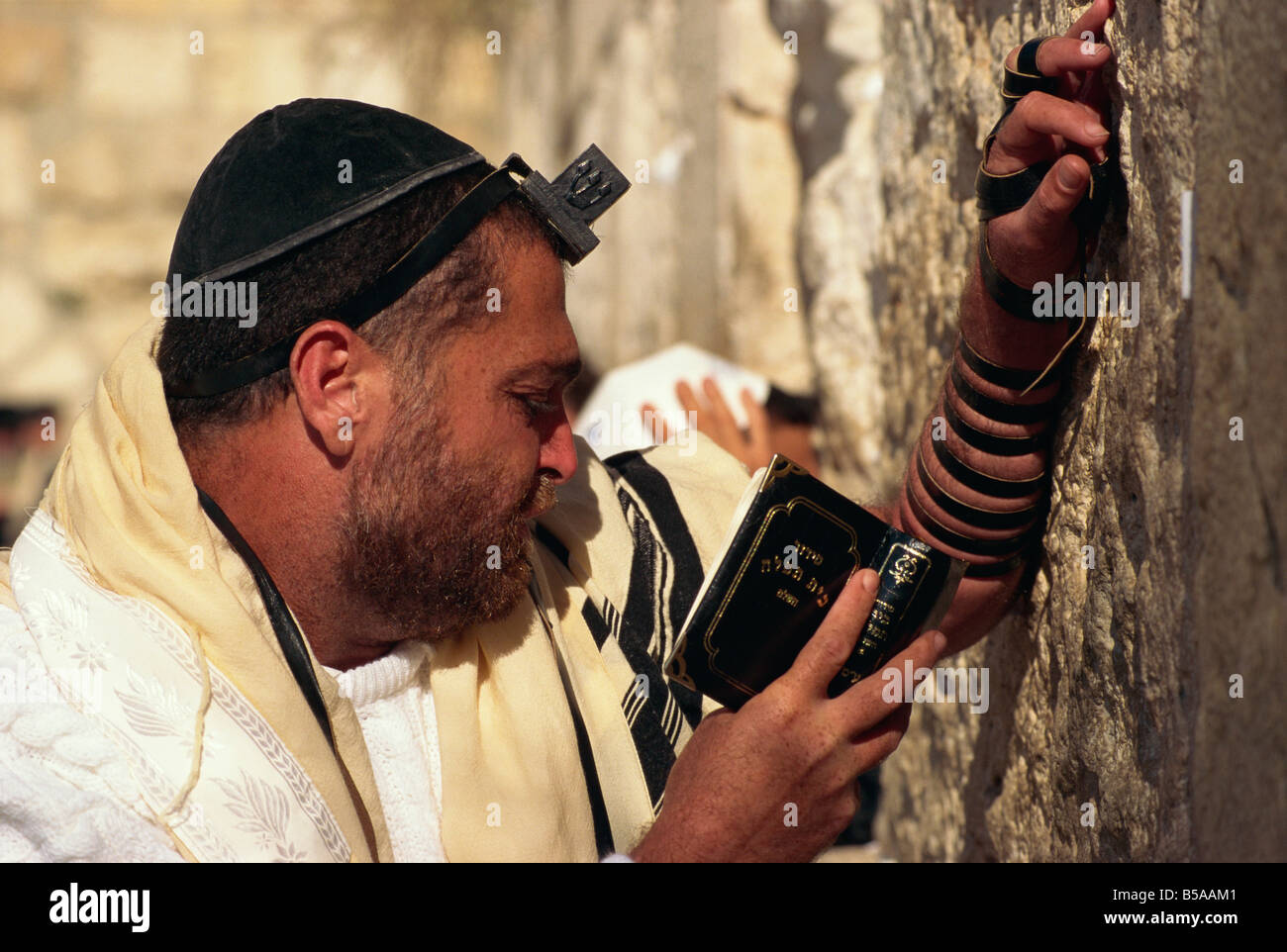 Close-up of Jew wearing shawl, skull cap and phylactery and holding a book, praying at the Western Wall in Jerusalem, - Stock Image