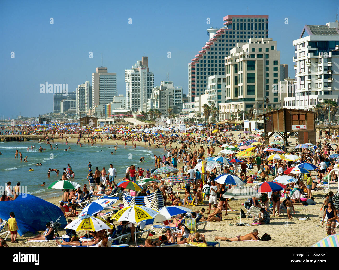 Crowds of tourists on the beach with tall seafront buildings, at Tel Aviv, Israel, Middle East - Stock Image
