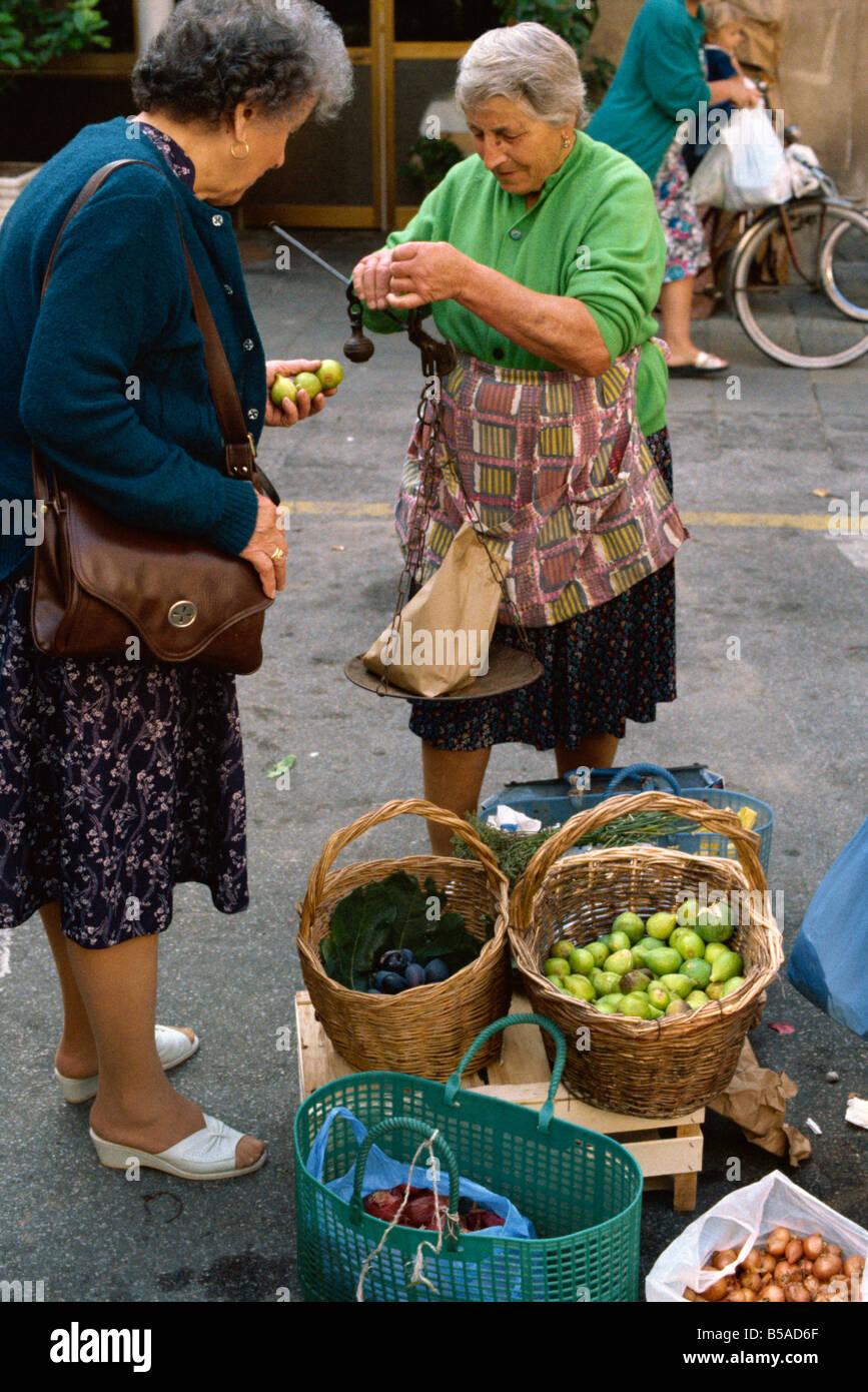 Woman selling figs with an old fashioned balance in the market at Pescia in Tuscany Italy M Newton - Stock Image