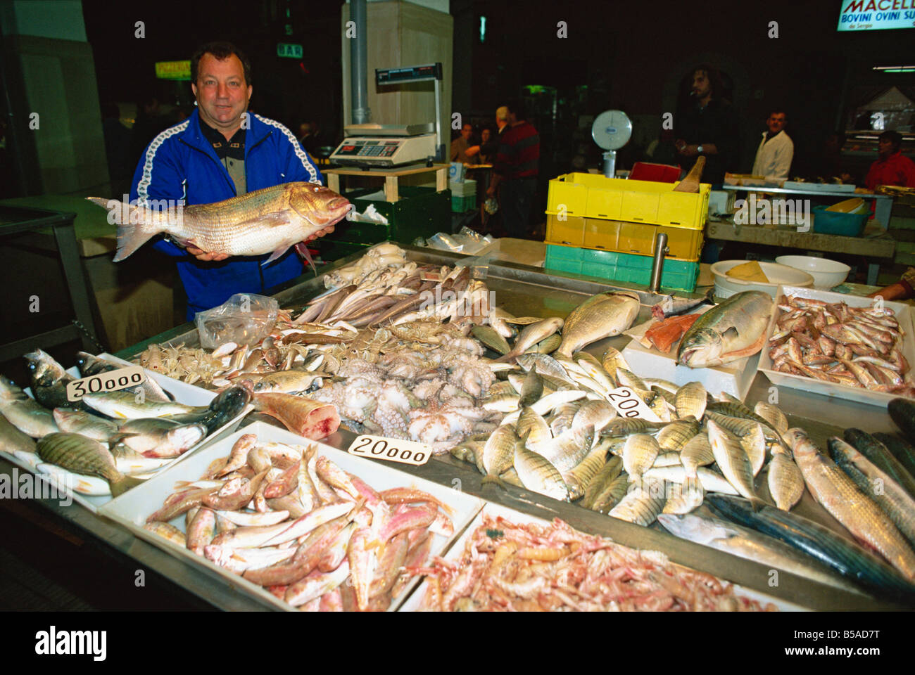 A fish monger at his stall on the harbour wall at Bisceglie in Puglia Italy M Newton - Stock Image