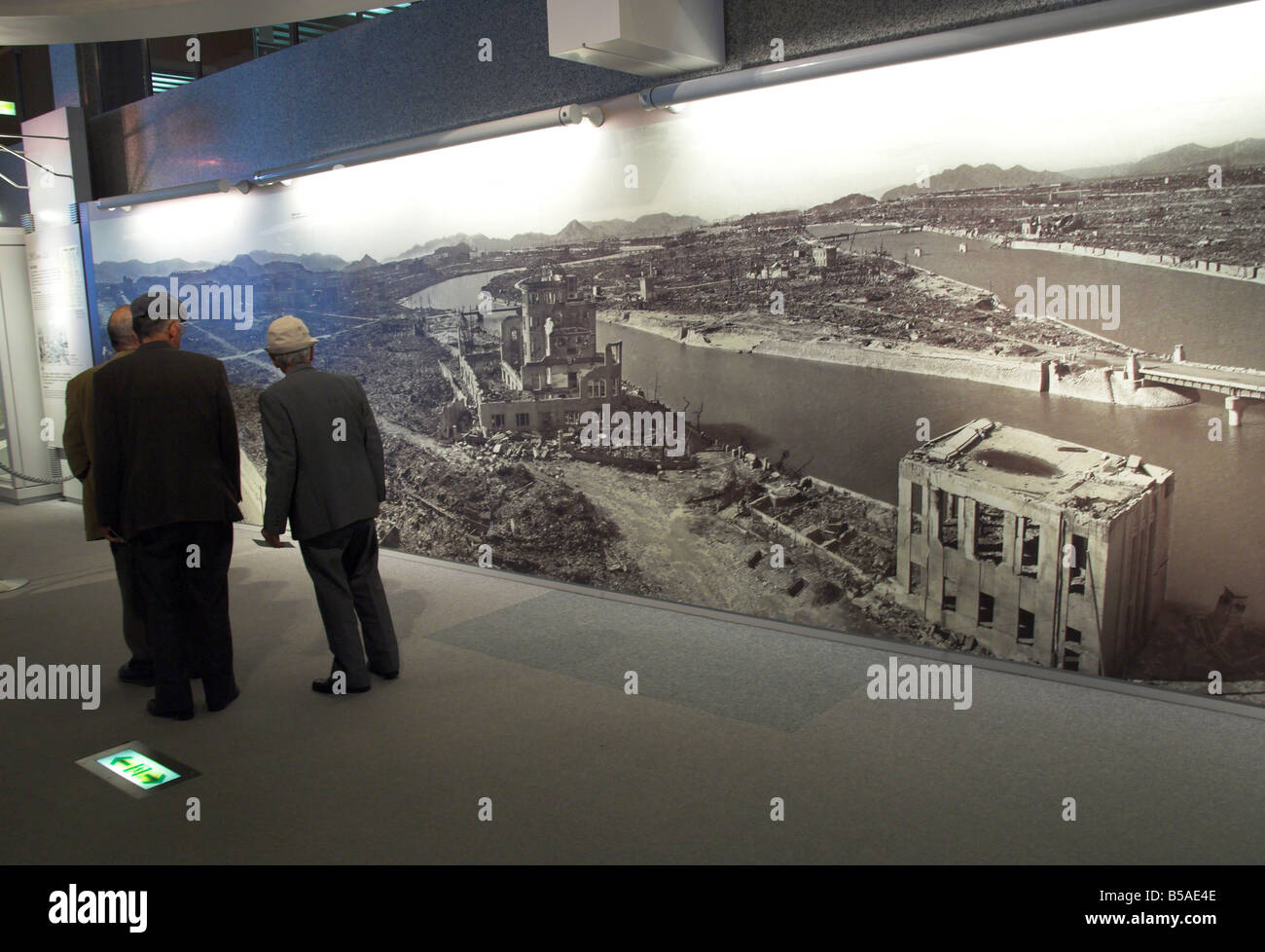 Visitors looking at huge wall poster showing the destruction of the city after the atomic bomb, Hiroshima, Honshu, - Stock Image