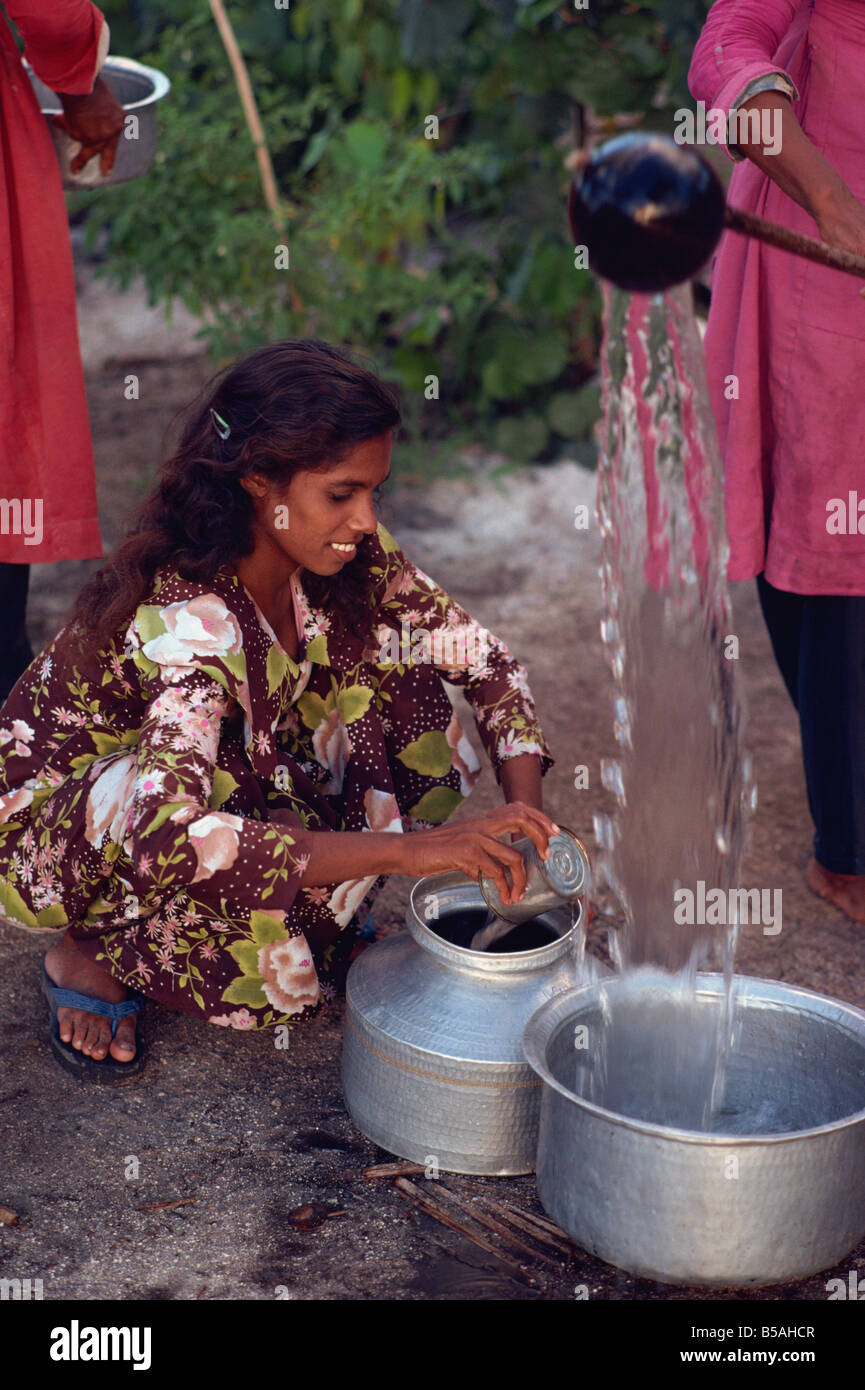 Women collecting water, Maldive Islands, Indian Ocean - Stock Image