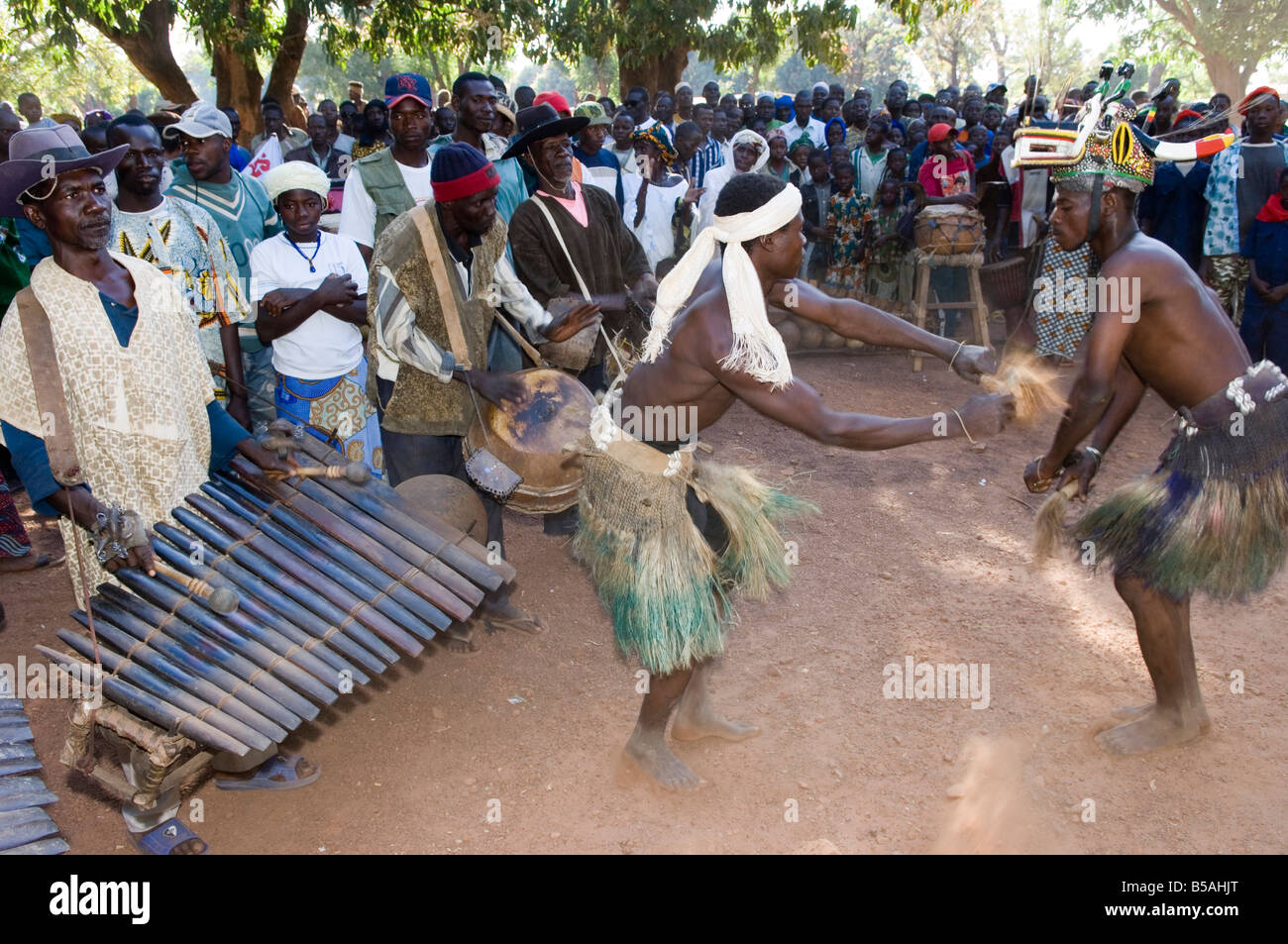 Senoufo masked dancer and musicians at festivities, Loulouni Village, Sikasso area, Mali, Africa - Stock Image