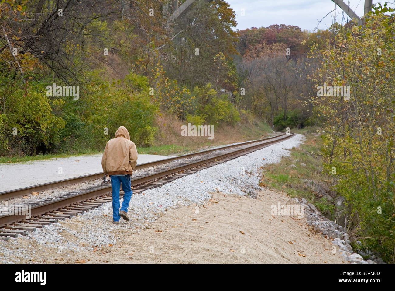 Man Walks Along Railroad Tracks - Stock Image