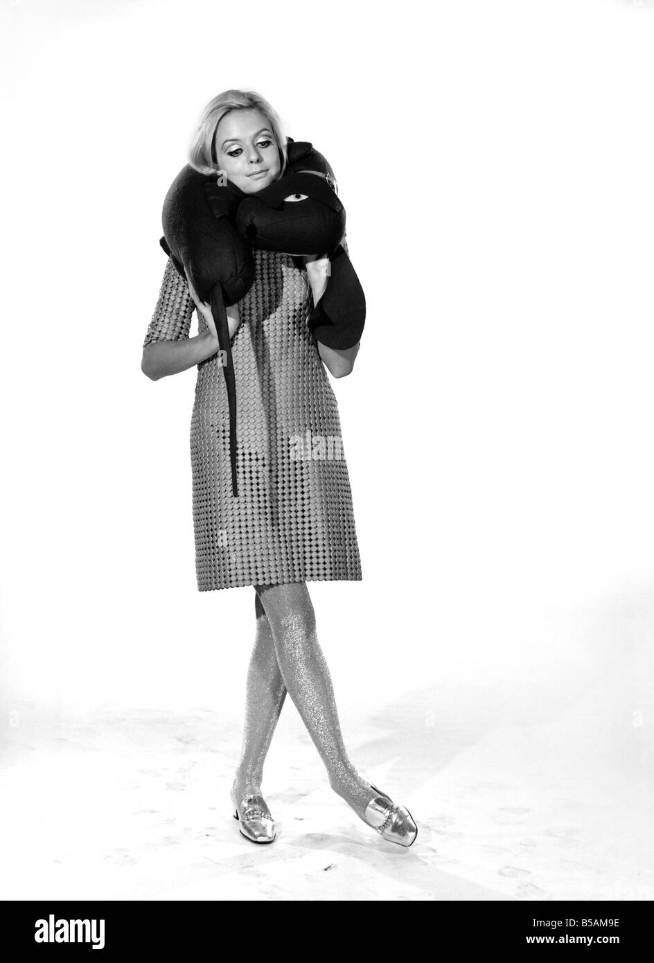 Model Anna Maria Greaves with Roly dog soft toy and draft excluder. 1959 D169-002 - Stock Image