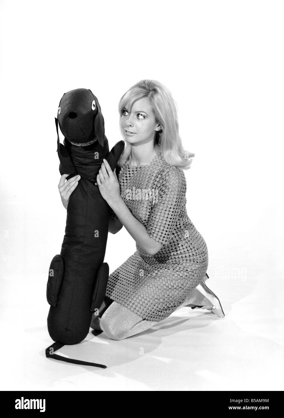 Model Anna Maria Greaves with Roly dog soft toy and draft excluder. 1959 D169-005 - Stock Image