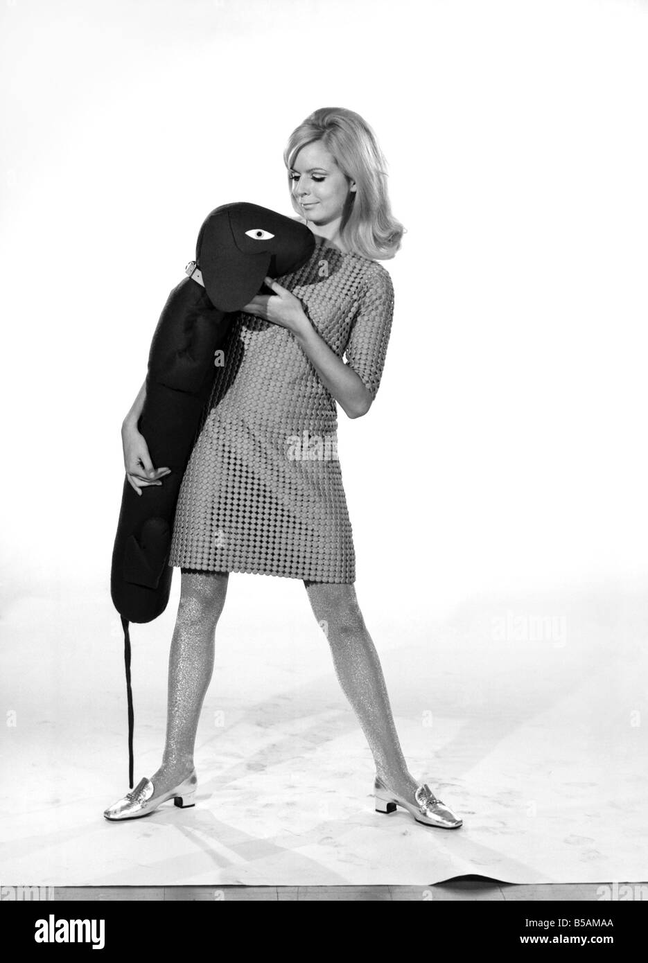 Model Anna Maria Greaves with Roly dog soft toy and draft excluder. 1959 D169-012 - Stock Image