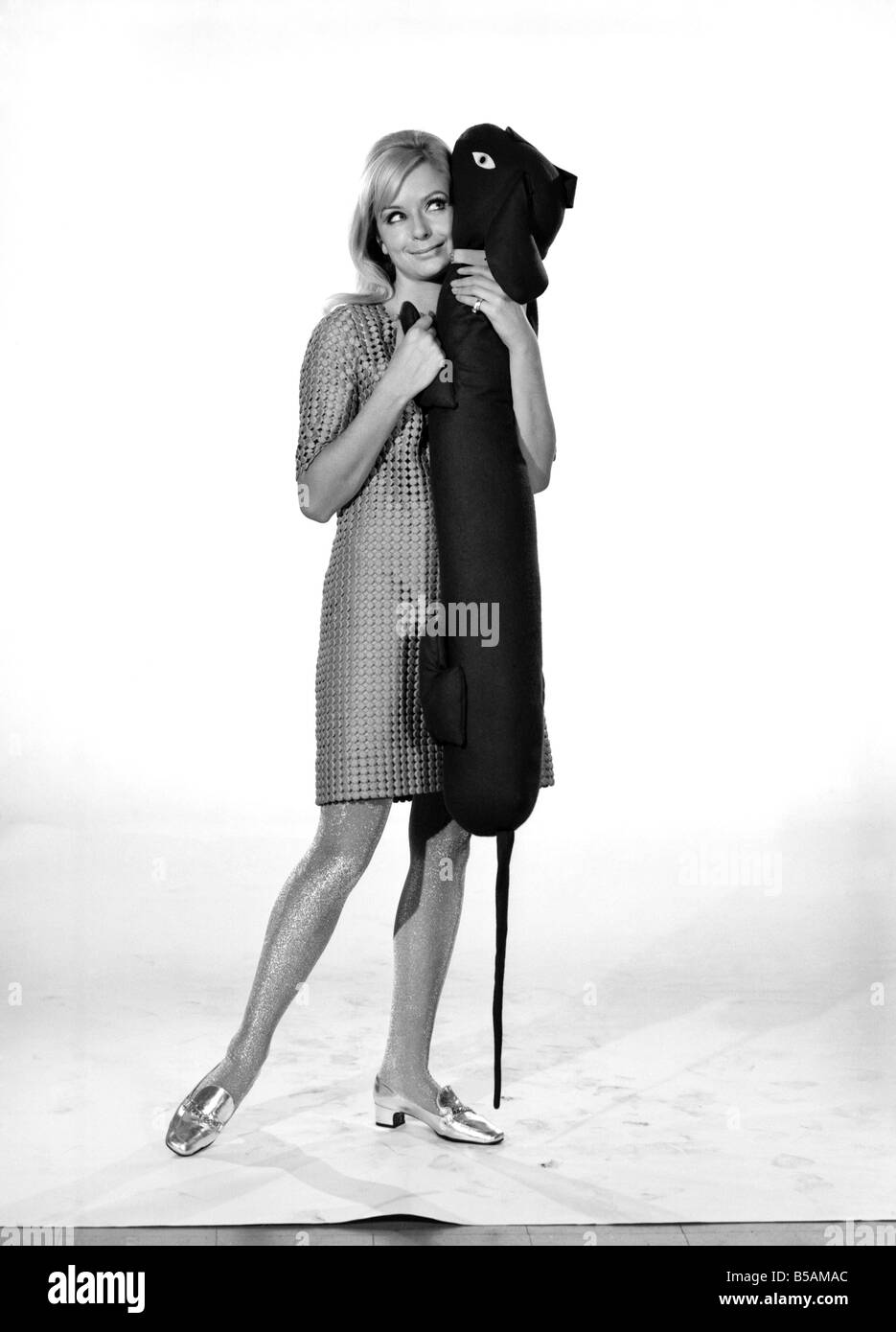 Model Anna Maria Greaves with Roly dog soft toy and draft excluder. 1959 D169-013 - Stock Image