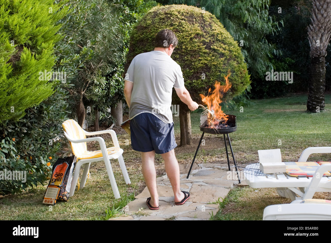 Landscape view of a man lighting a BBQ in a garden & Landscape view of a man lighting a BBQ in a garden Stock Photo ...