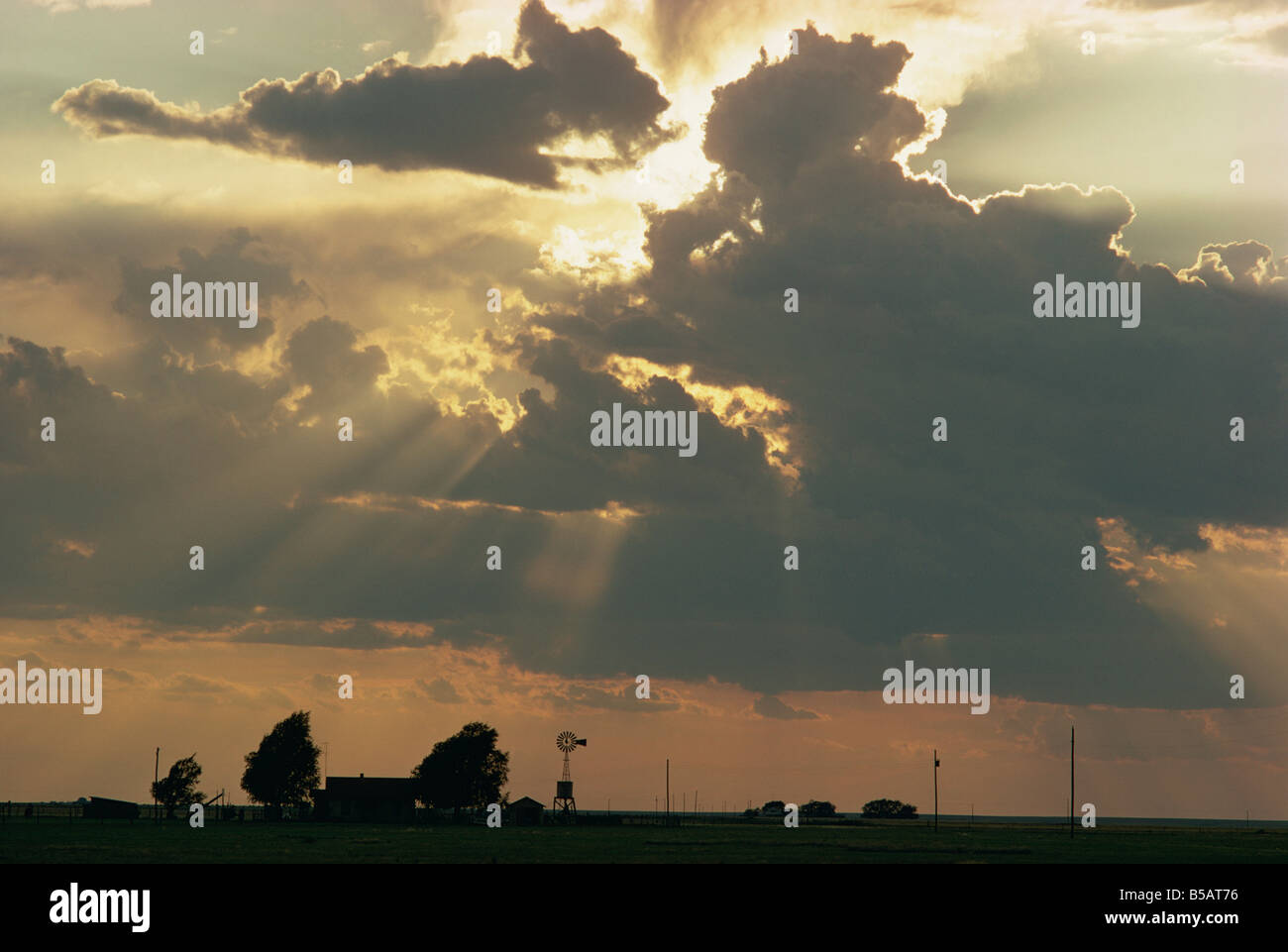 Rays of sun light landscape from behind dark towering clouds - Stock Image