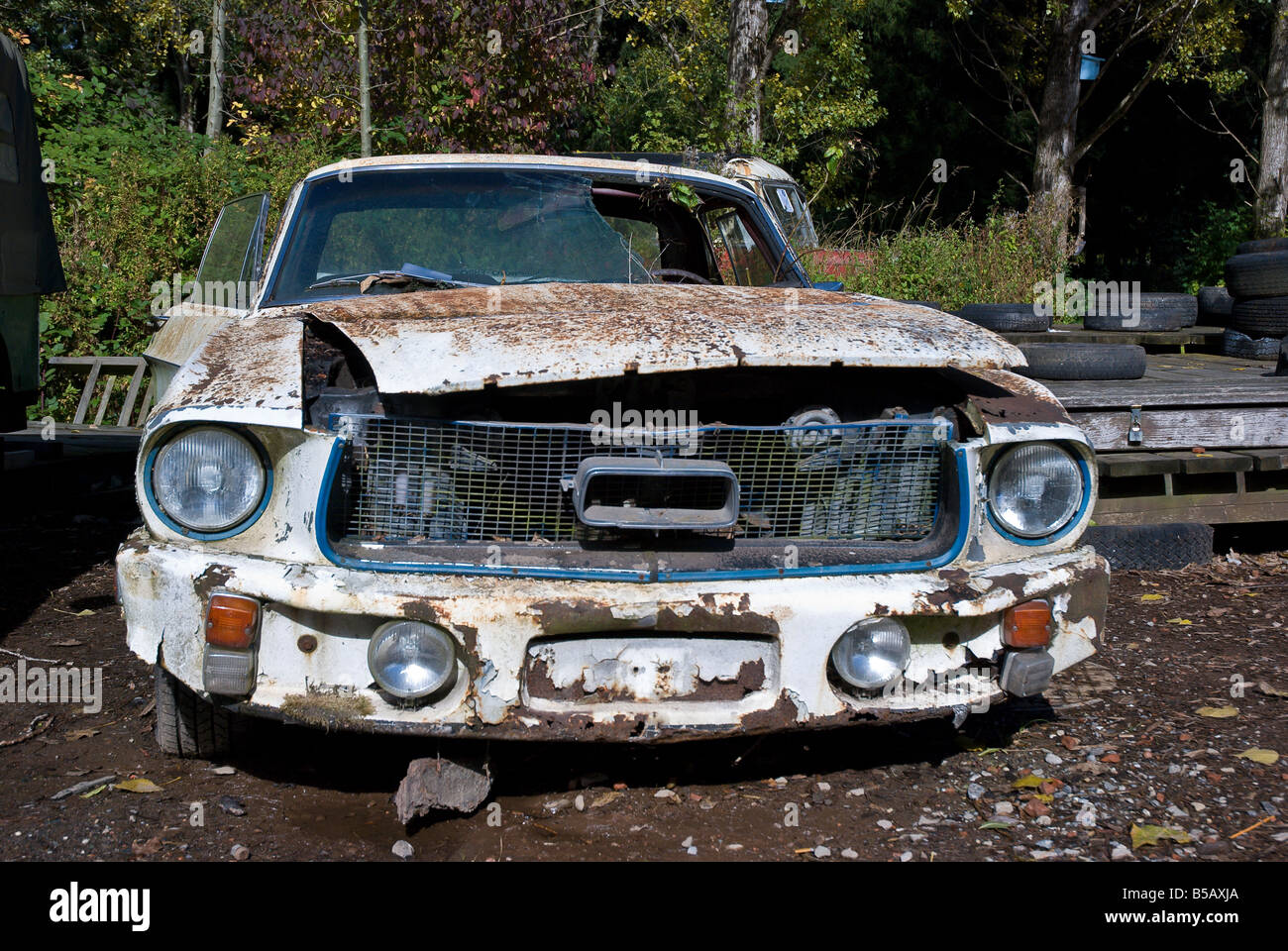 An old ford mustang sits in the junkyard