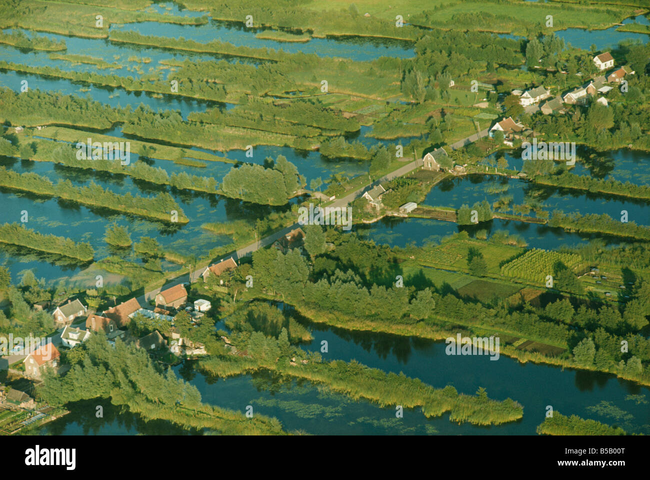 Aerial of a road across a landscape of water and tree lined embankments between Haquet and  Utrecht in the Netherlands, Stock Photo