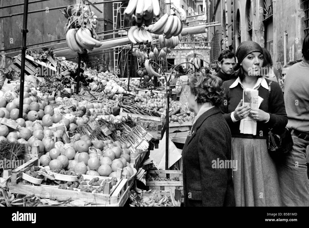 Woman buying fresh fruit and vegetables in a poor suburb on the outskirts of Rome, Italy
