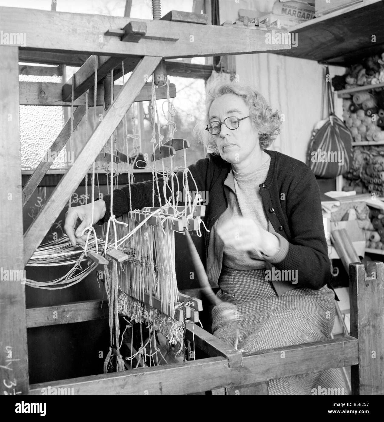 Woman seen here working at a loom weaving. 1955 - Stock Image