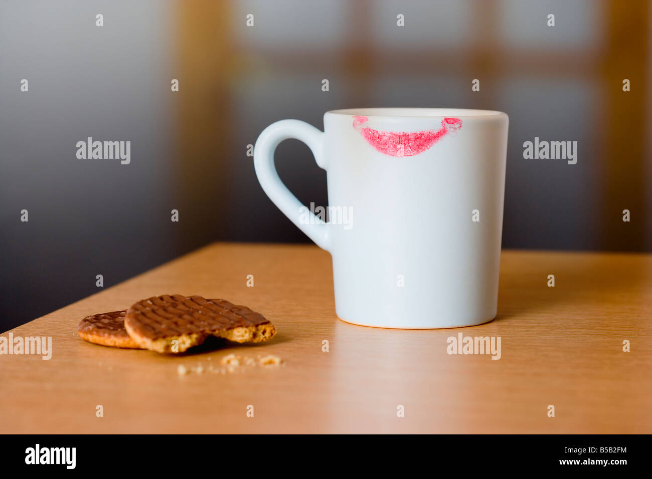 Coffee mug with lipstick mark and chocolate biscuits on table - Stock Image
