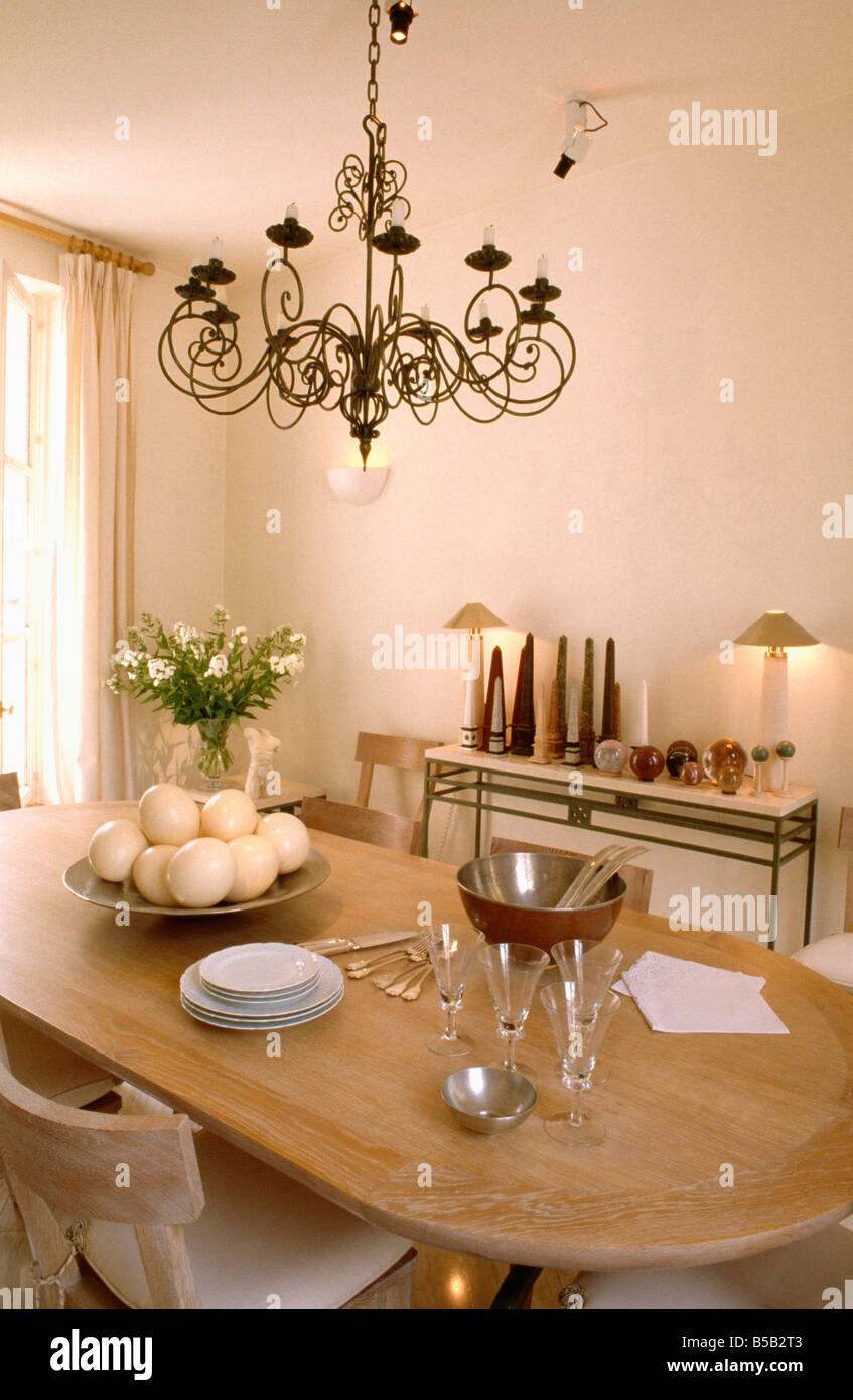 Metal Chandelier Above Limed Table With Bowl Of Ostrich Eggs And Cutlery In Dining  Room With Lighted Lamps On Console Table