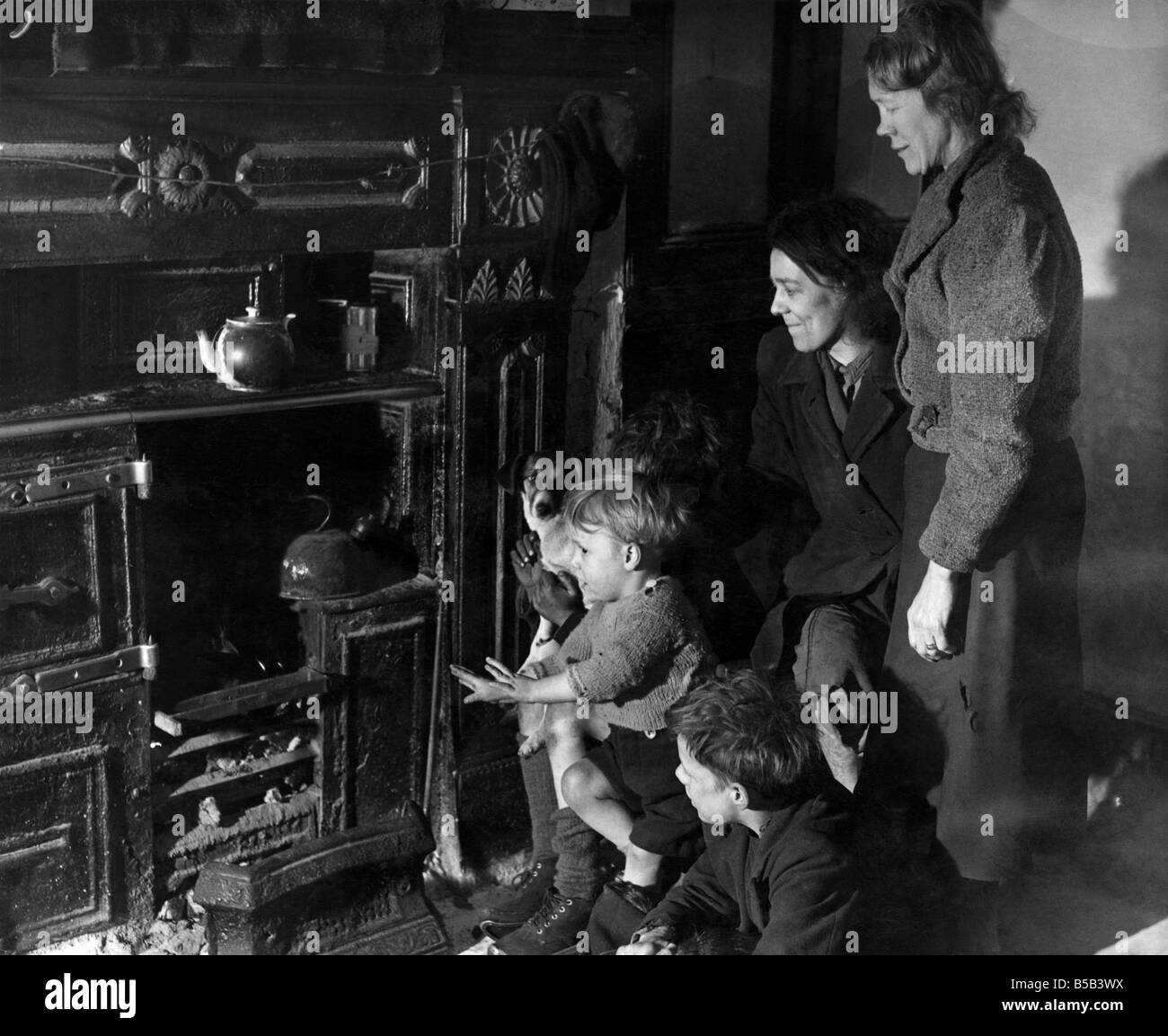 Jean Kerwin of Chorlton-on-Medlock calls in her neighbour, Mrs. Lydia Fox, to share their fire. ;They've been - Stock Image