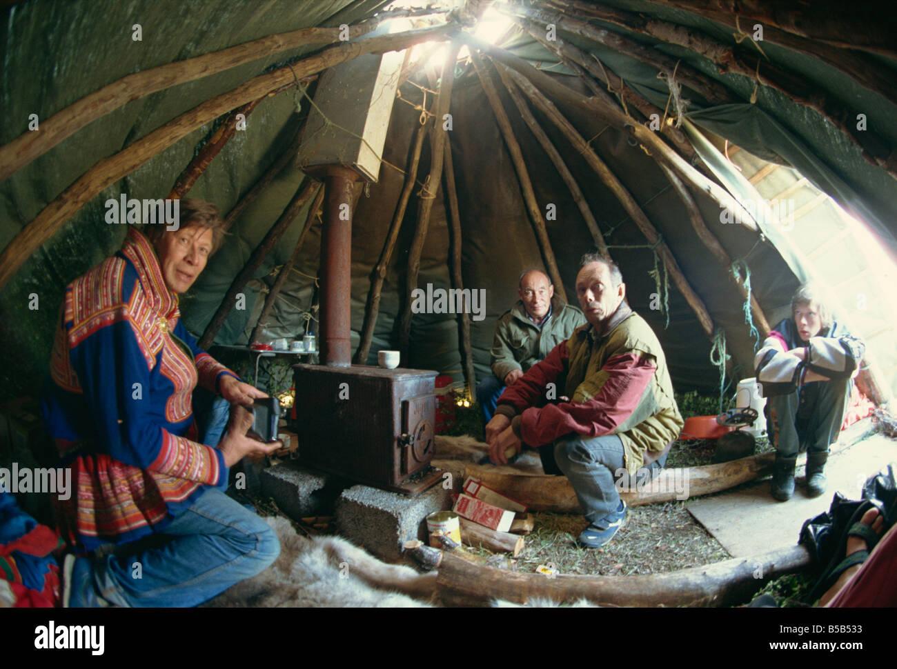 Sami man (Lapplander) inside laavo (tent), drinking moonshine, Finnmark, Norway, Scandinavia, Europe - Stock Image